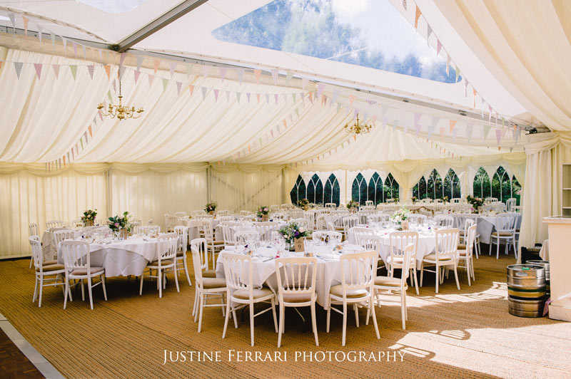 Inside of Marquee with dining tables decorated in cream with bunting